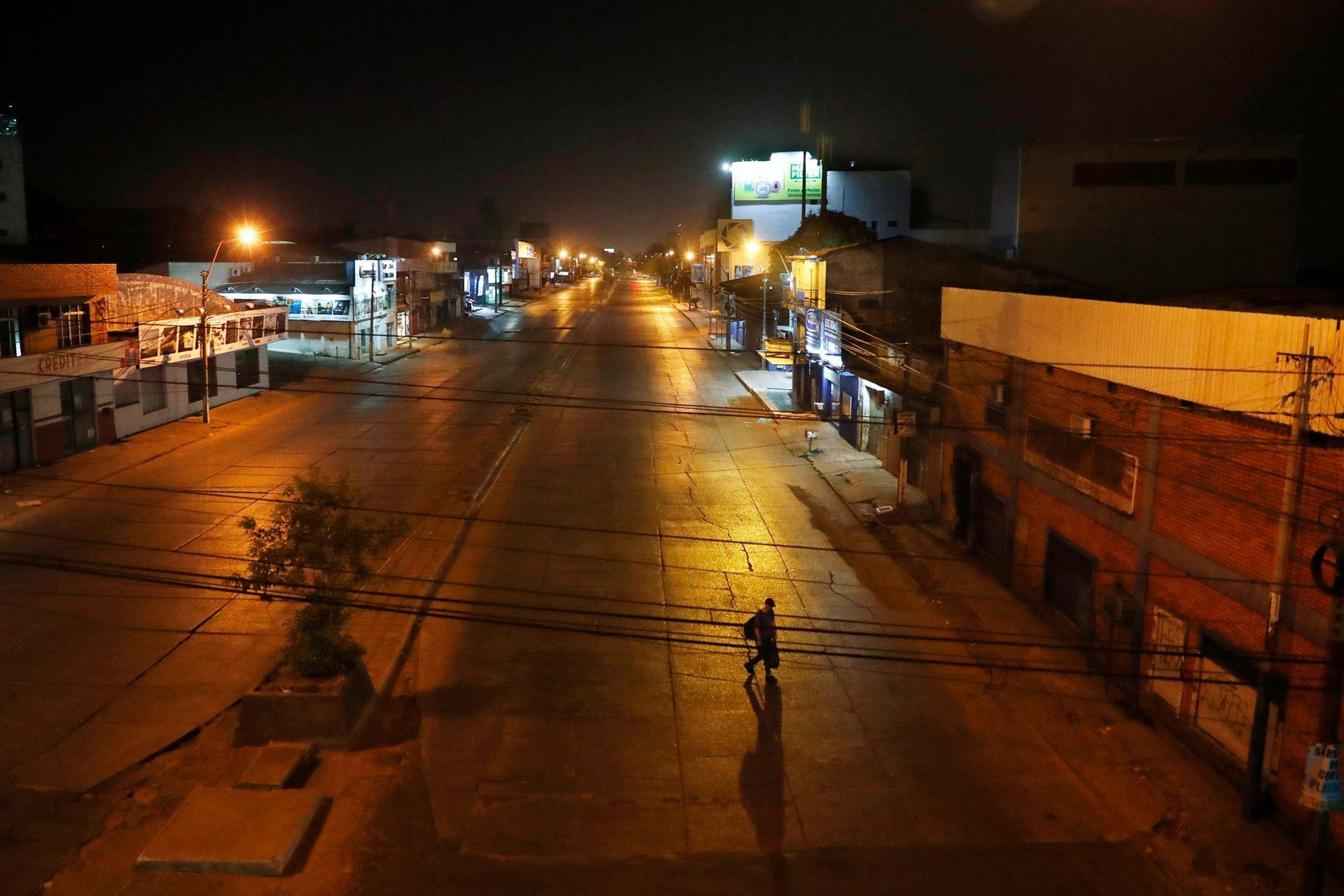 Un hombre cruza una avenida vacía de Eusebio Ayala durante un toque de queda para frenar la nueva pandemia de coronavirus en Asunción