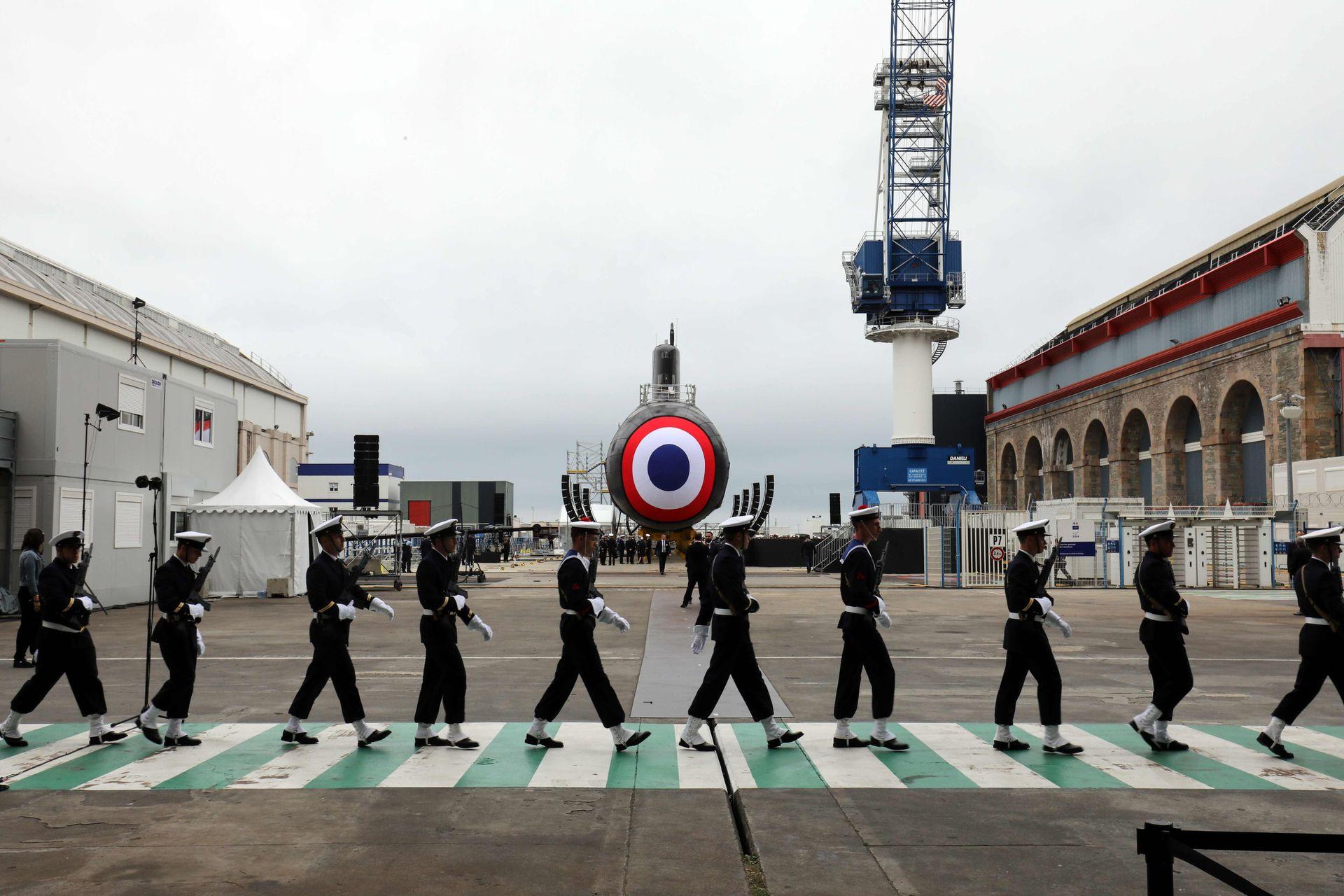 """Miembros de la Infantería de Marina Nacional francesa desfilan frente al nuevo submarino nuclear llamado """"Suffren"""" en el astillero del Grupo Naval en Cherbourg, en el noroeste de Francia"""