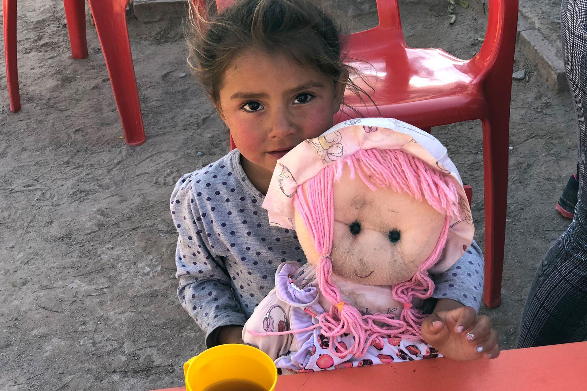 Una nena toma la merienda en el Espacio de Primera Infancia (EPI) de Manga Bajada junto a su muñeca. Consiste en mate cocido, libritos, alfajorcitos de maicena y facturas. El resto del tiempo reciben estimulación y atención médica.