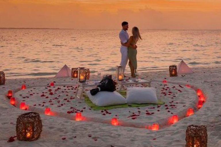 El futbolista y su novia se mostraron felices a orillas del mar y cerca de una corazón armado en la arena con velas rojas