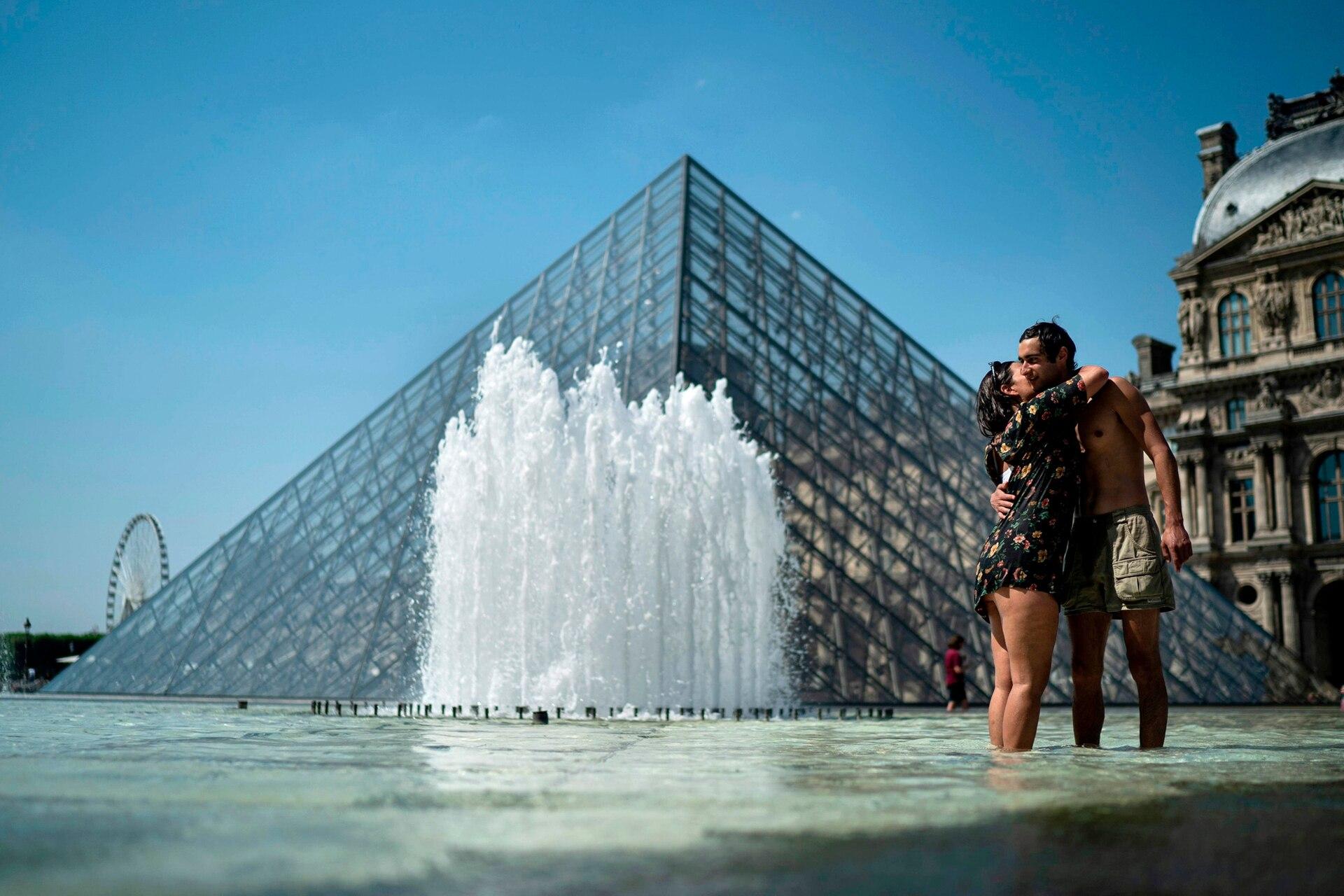 Abrazos en la fuente de la Pirámide del Louvre, en París