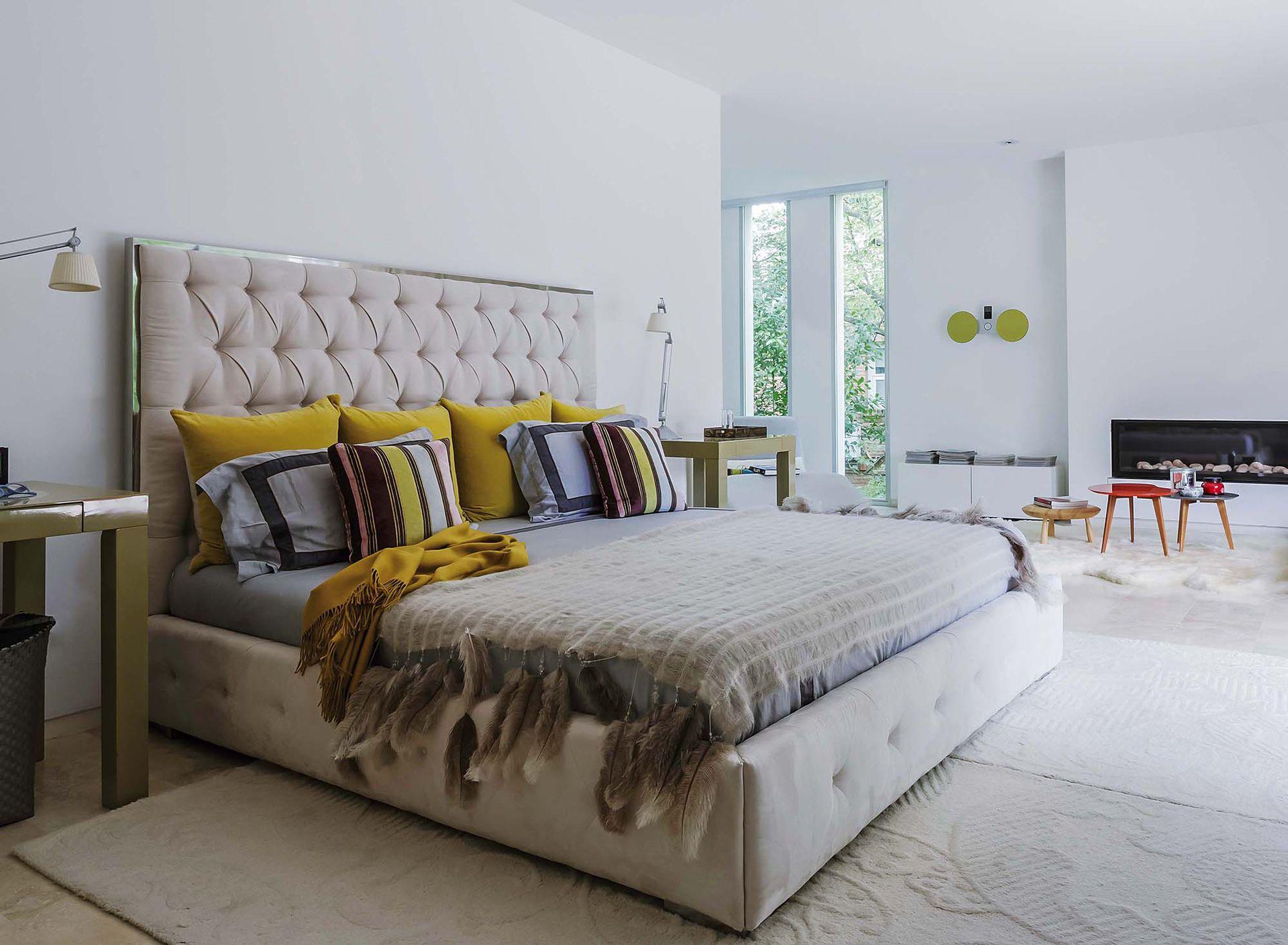 En la cama, pura calidez con tejidos, plumas y una manta color mostaza de Sekkei.