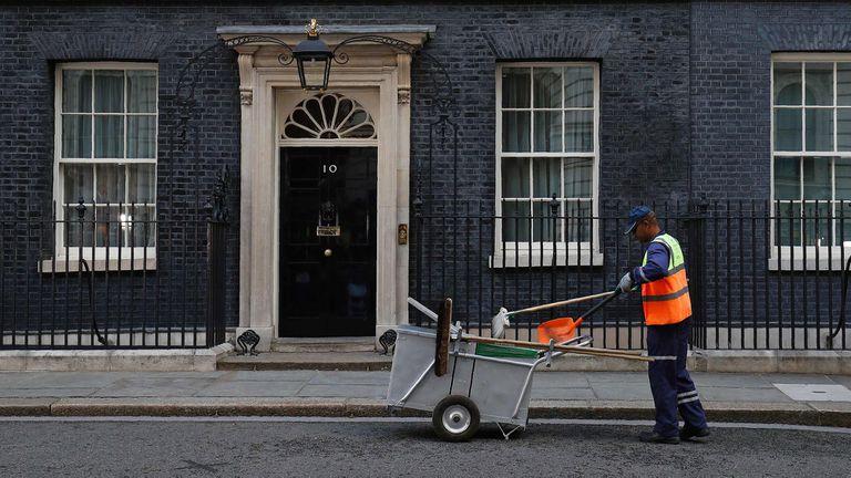 Un trabajador de Westminster limpia Downing Street a la altura de la residencia oficial de la primera ministra Theresa May; todos los ojos están puestos en qué pasará tras las elecciones