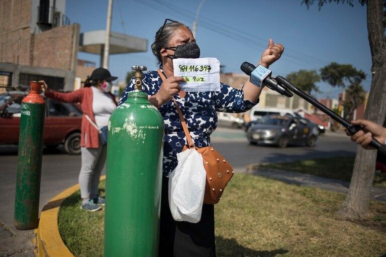 Lidia Ruiz habla con un reportero junto al tanque de oxígeno recién llenado para su hermana que sufre de COVID-19, en Callao, Perú