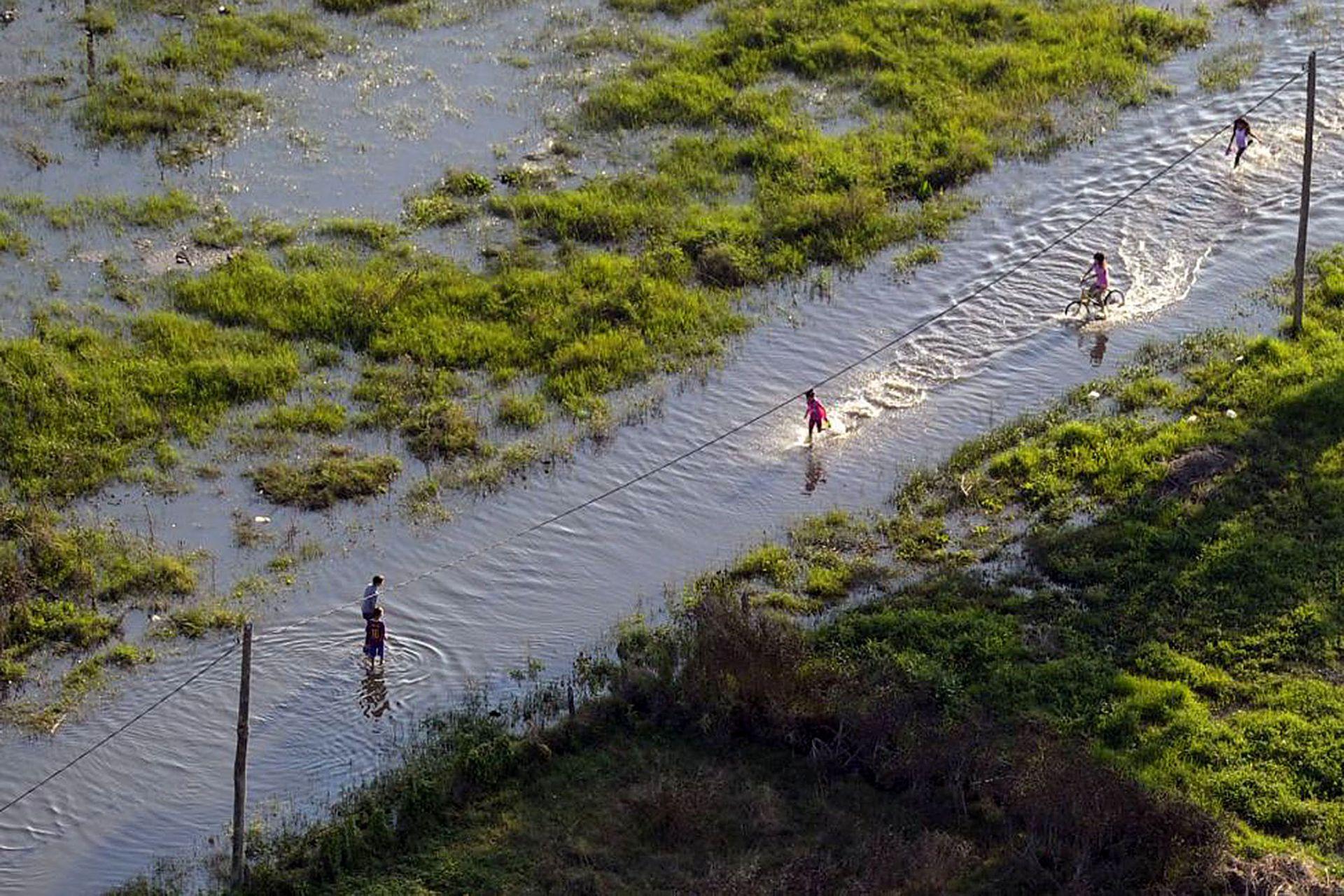 Algunos niños juegan en una zona inundada en las afueras de la ciudad de La Plata