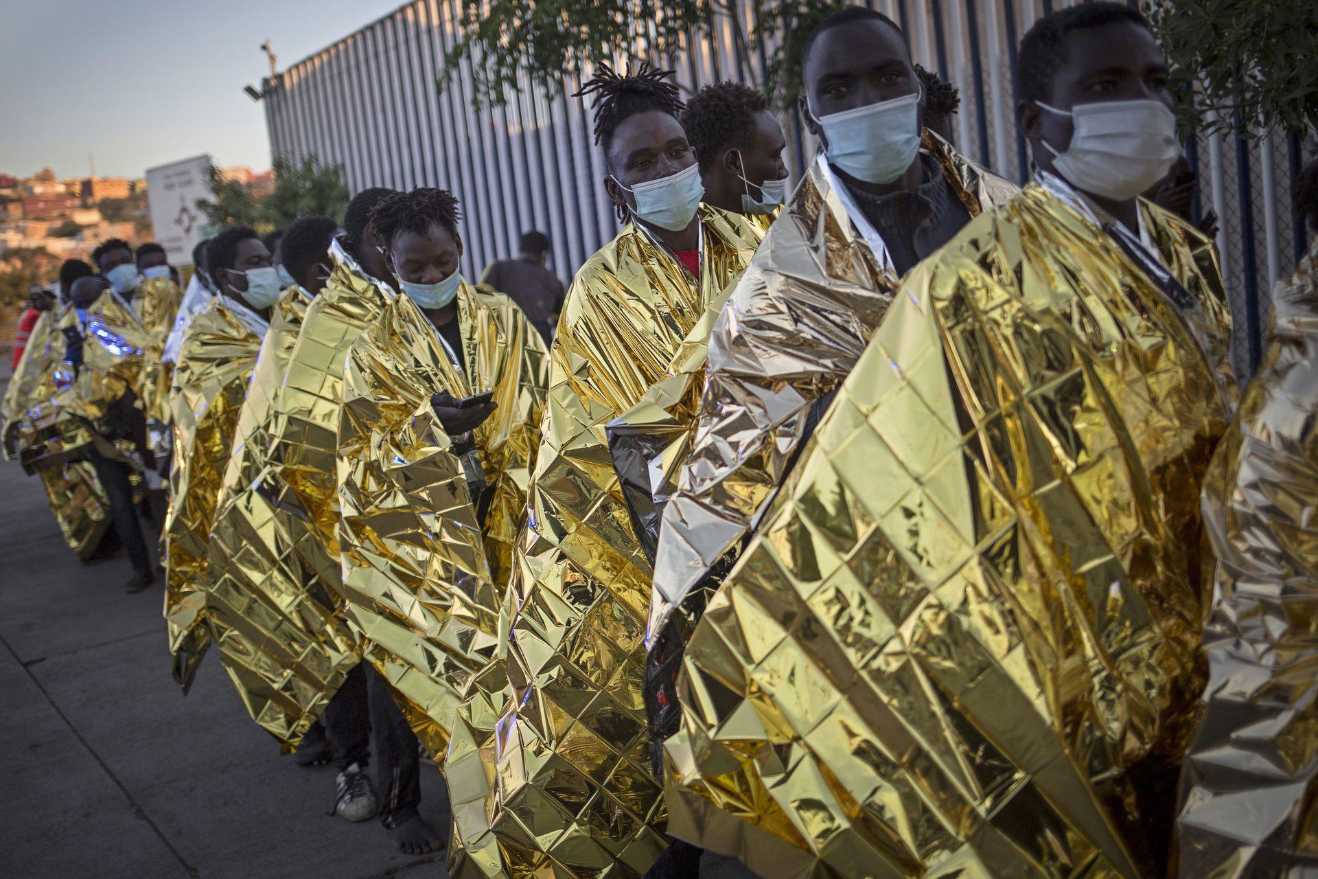 Un grupo de migrantes camina envueltos en mantas térmicas en un centro de detención para migrantes