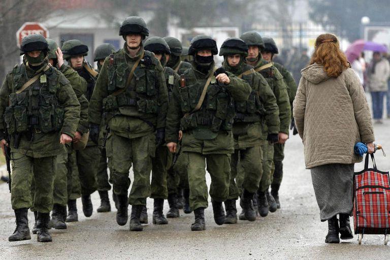 Soldados no identificados, que responden al ejército ruso, caminan por la ciudad de Perelvanoye, en la región de Crimea