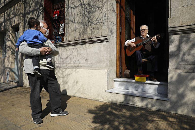 El Tata Cedrón toca su música para los vecinos desde el zaguán de su casa, en Villa del Parque