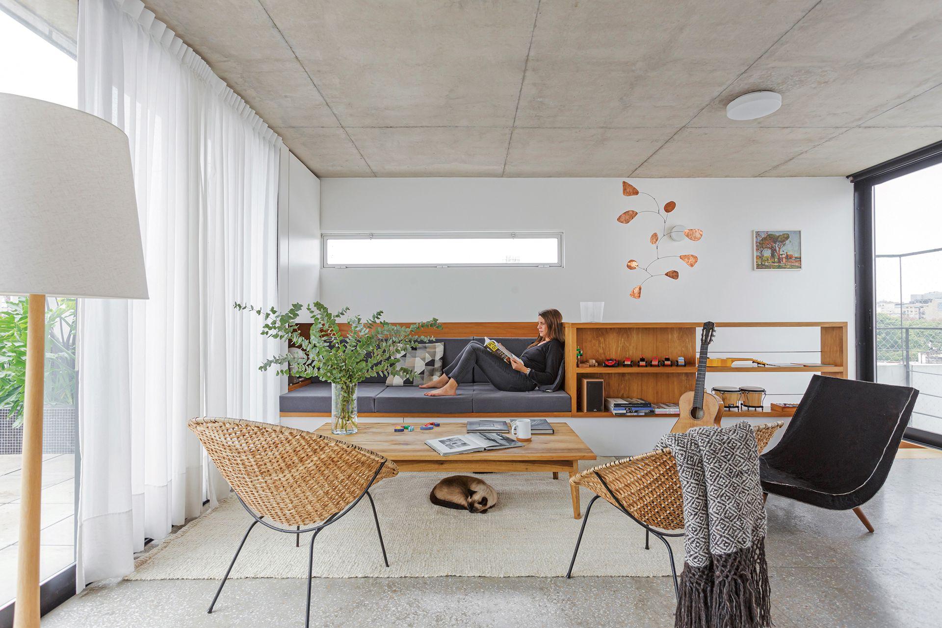 Lámpara de pie (Objetos Luminosos), mesa baja y sillón individual (Net Muebles). Móvil de bronce (Objetos Móviles). Sillones de mimbre y hierro (Mercado de Pulgas) y manta tejida en telar (Elementos Argentinos).
