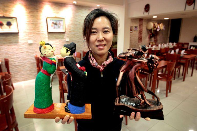 Flores: Hye Hyun Son, o Alexandra, y las efigies de dos parejas en bailes típicos: una, coreana; la otra, argentina