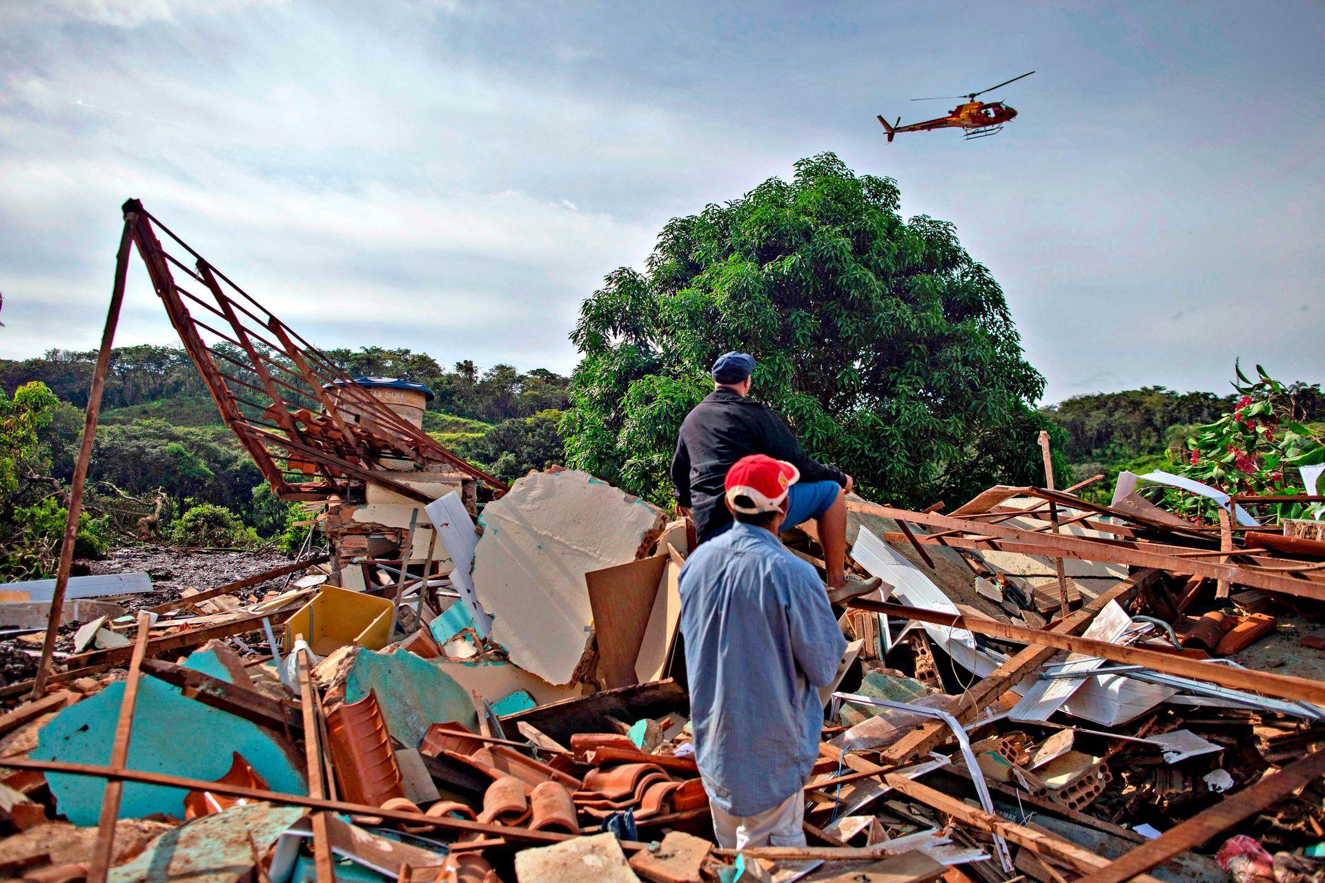 La gente de la comunidad de Parque da Cachoeira mira un helicóptero de bomberos que vuela sobre el área afectada por el lodo un día después del derrumbe de una represa en una mina de mineral de hierro