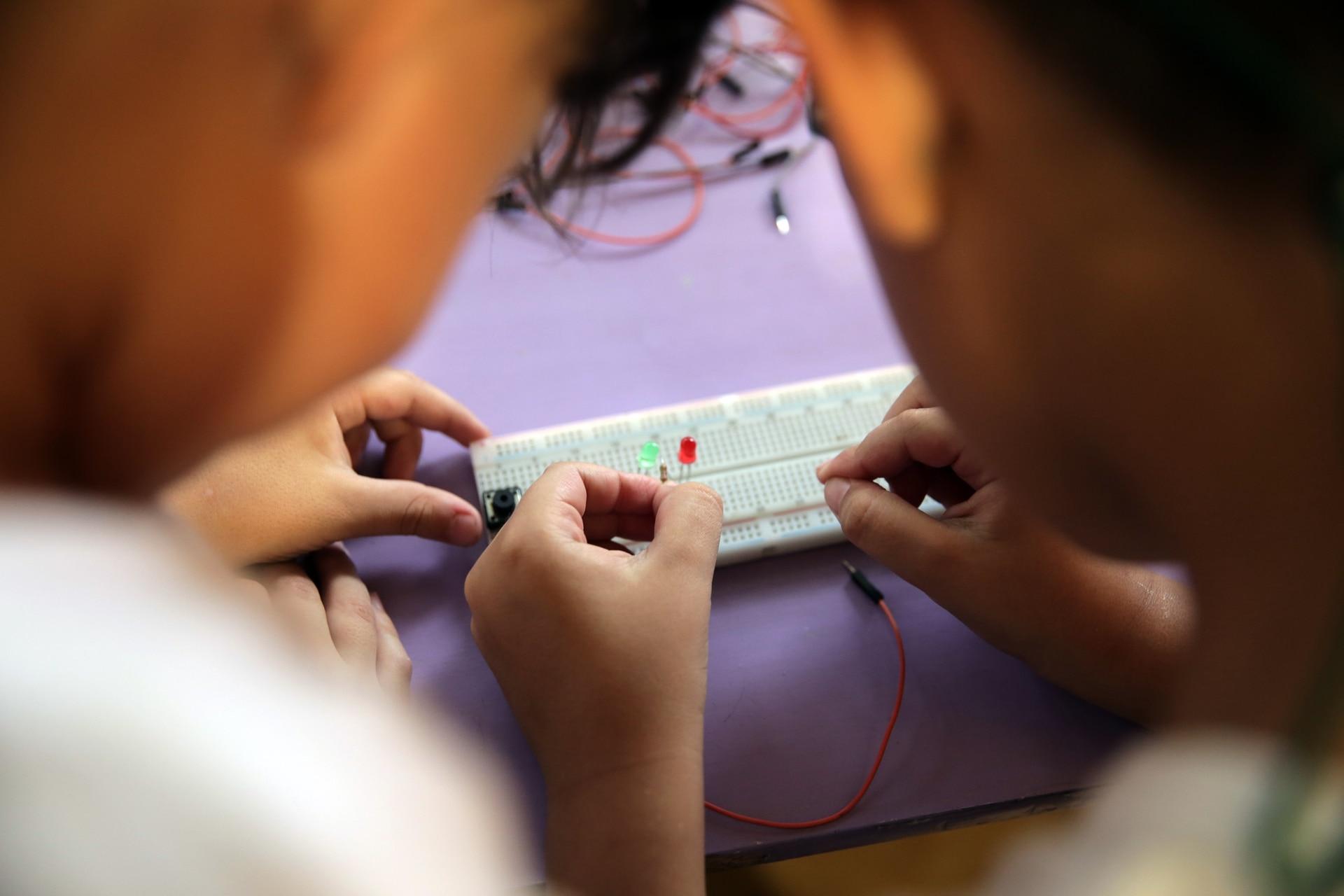 Los chicos trabajando en un proyecto de mecatrónica, comparten roles y colaboran entre ellos.