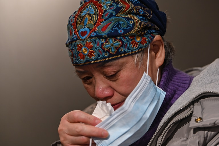 Esta foto tomada el 25 de noviembre de 2020 muestra a Zhong Hanneng secándose las lágrimas mientras habla de su hijo que murió de Covid-19 en Wuhan, provincia central de Hubei en China