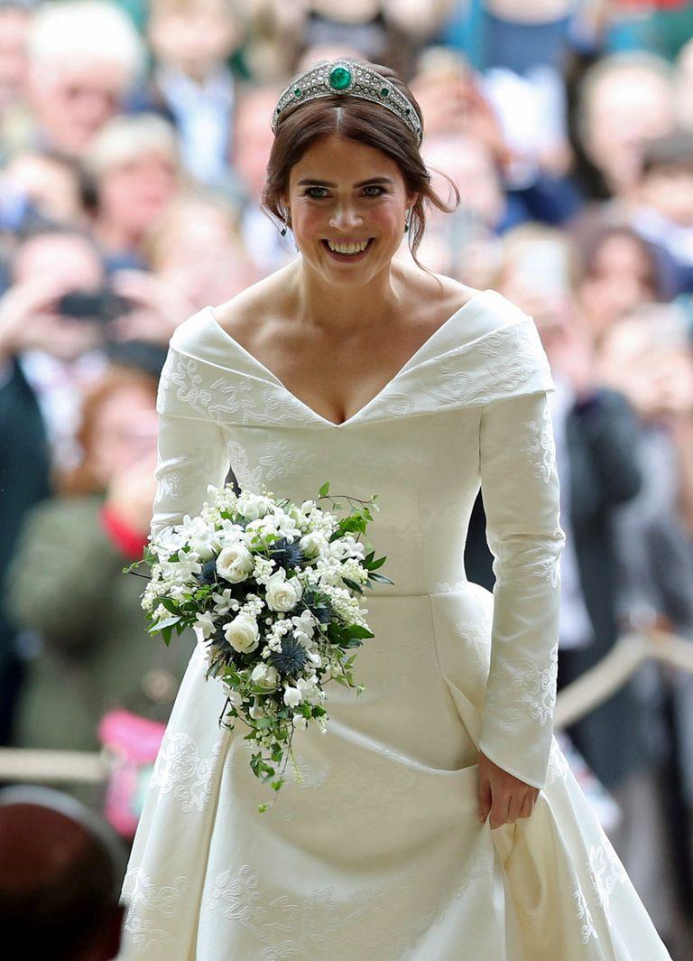 """Radiante, sin velo y rompiendo tradiciones, Eugenia llevó un vestido de doble escote en """"V"""" y falda abullonada, de Peter Pilotto. Sobre la falda, en brocado, la rosa de York, un guiño a la Reina; el trébol de Irlanda, origen de la familia Ferguson, y la hiedra, signo de su casa."""