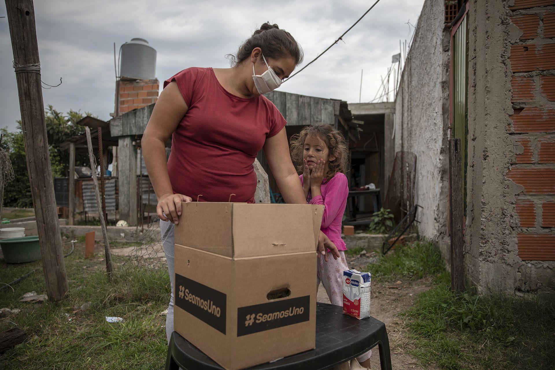 Una familia recibe una caja de asistencia de la iniciativa SeamosUno, en José C. Paz