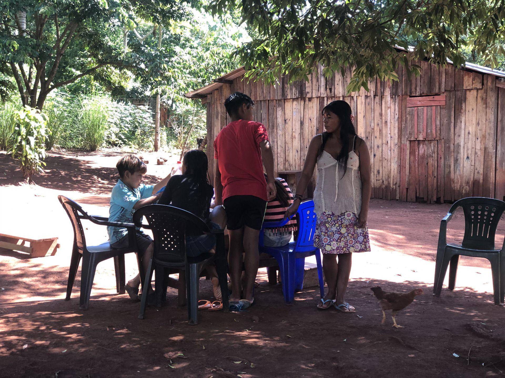 Lilian y sus hermanos hacen la tarea a la sombra de un árbol en el patio de su casa
