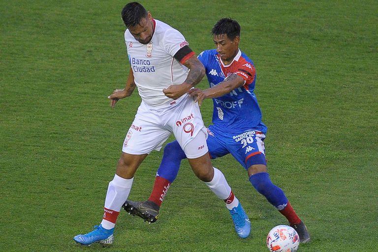 Andrés Chávez disputa la pelota con Martín Cañete durante el partido que disputan Huracán y Unión de Santa Fe.