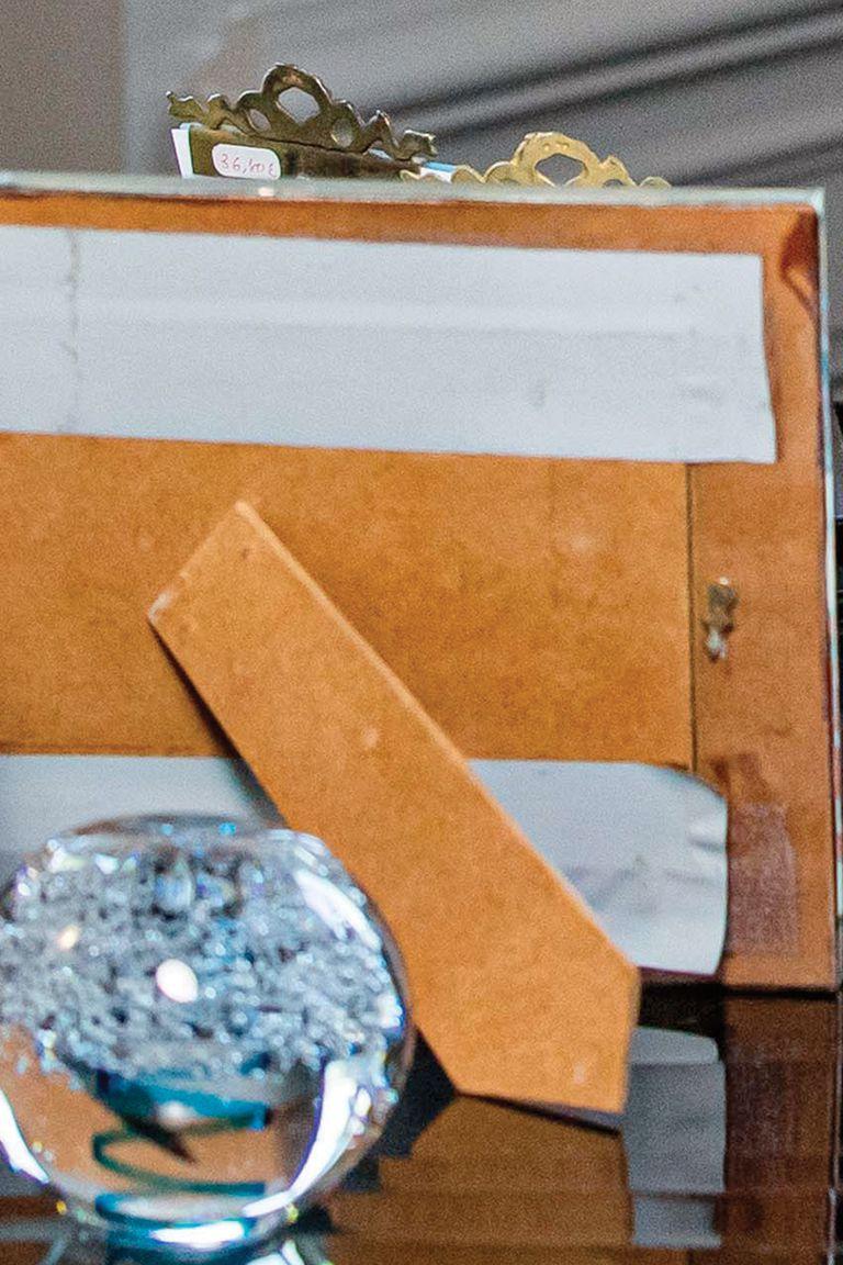Arriba del escritorio hay un portarretratos de madera arreglado de forma casera con cinta, y dos con marco de cobre que aún tienen el precio pegado: 36,80 euros.