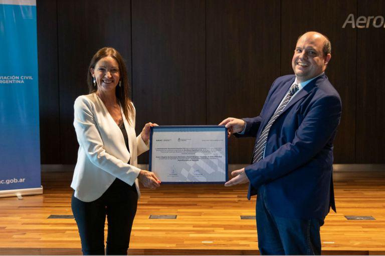 Paola Tamburelli le entregó a Pablo Ceriani, presidente de Aerolíneas el certificado que lo habilita a operar bajo el mismo código que Austral