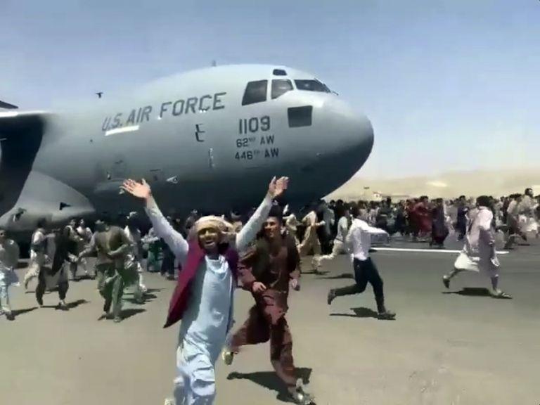 Cientos de personas corren tratando de treparse al avión militar estadounidense que despegaba de Kabul