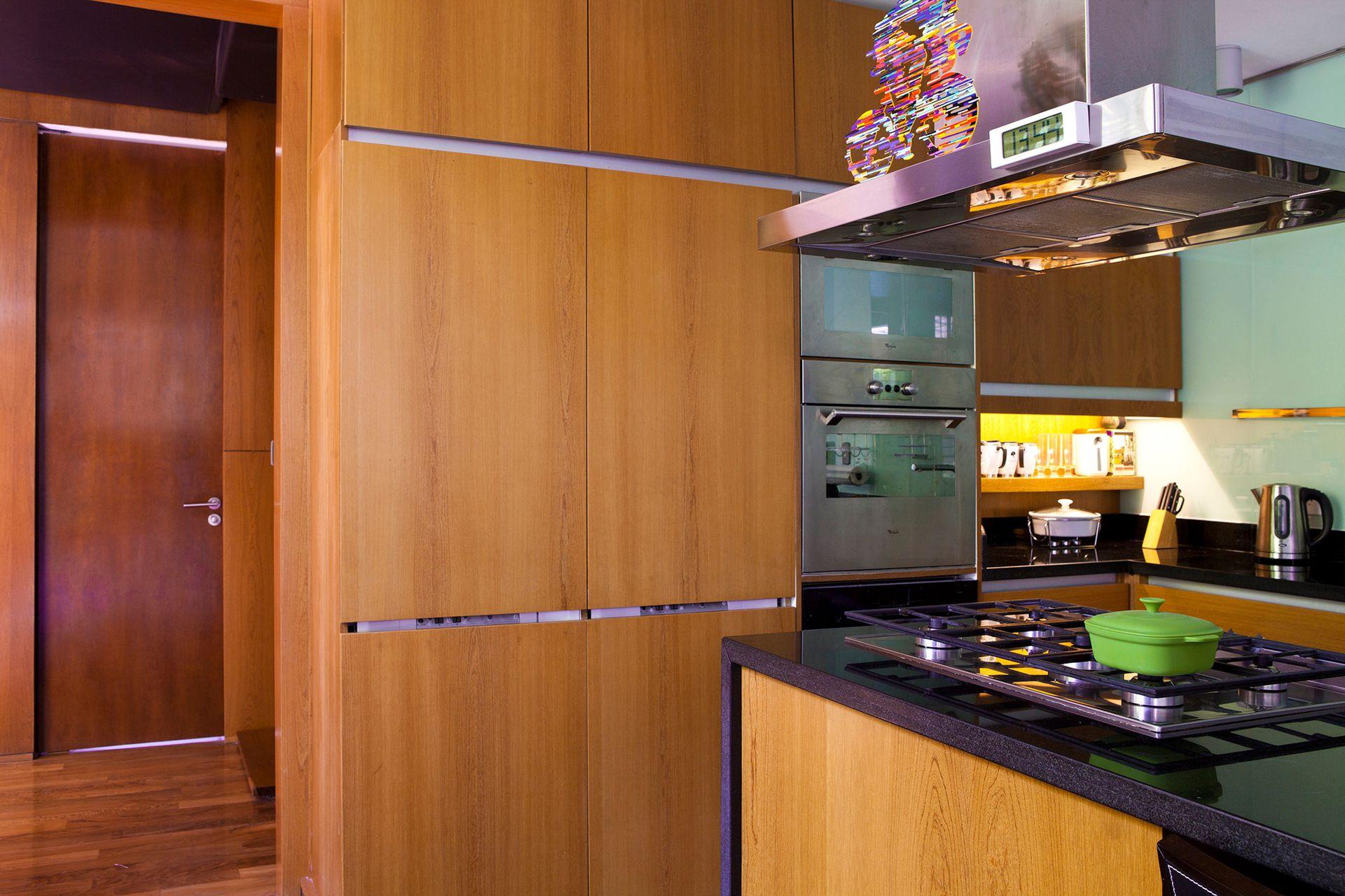 Con los metros justos, la cocina es sensacional. Tiene paneles de madera de un tinte dorado que esconden hasta las heladeras.