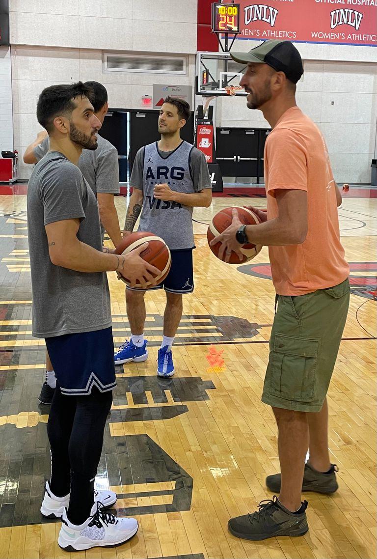Emanuel Ginóbili conversa con Facundo Campazzo en el predio de entrenamiento de Las Vegas, donde el seleccionado argentino de básquetbol se preparó para los Juegos Olímpicos de Tokio; detrás, Nicolás Laprovittola