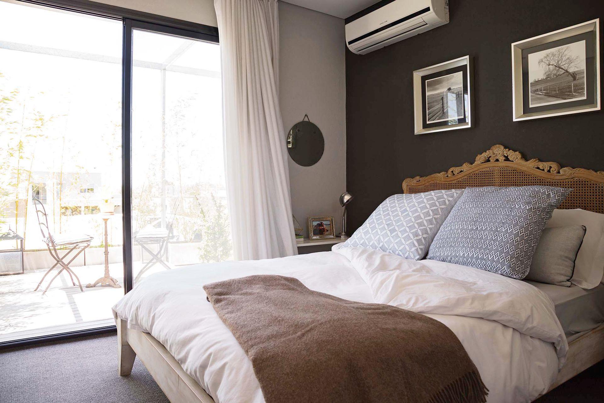 Sobre la cama, manta de lana traída de Lima y almohadones con fundas francesas pintadas a mano.