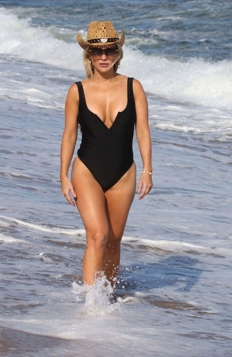 El look playero de Alejandra Maglietti: malla enteriza negra con escote en v, sombrero de arpillera y lentes de sol