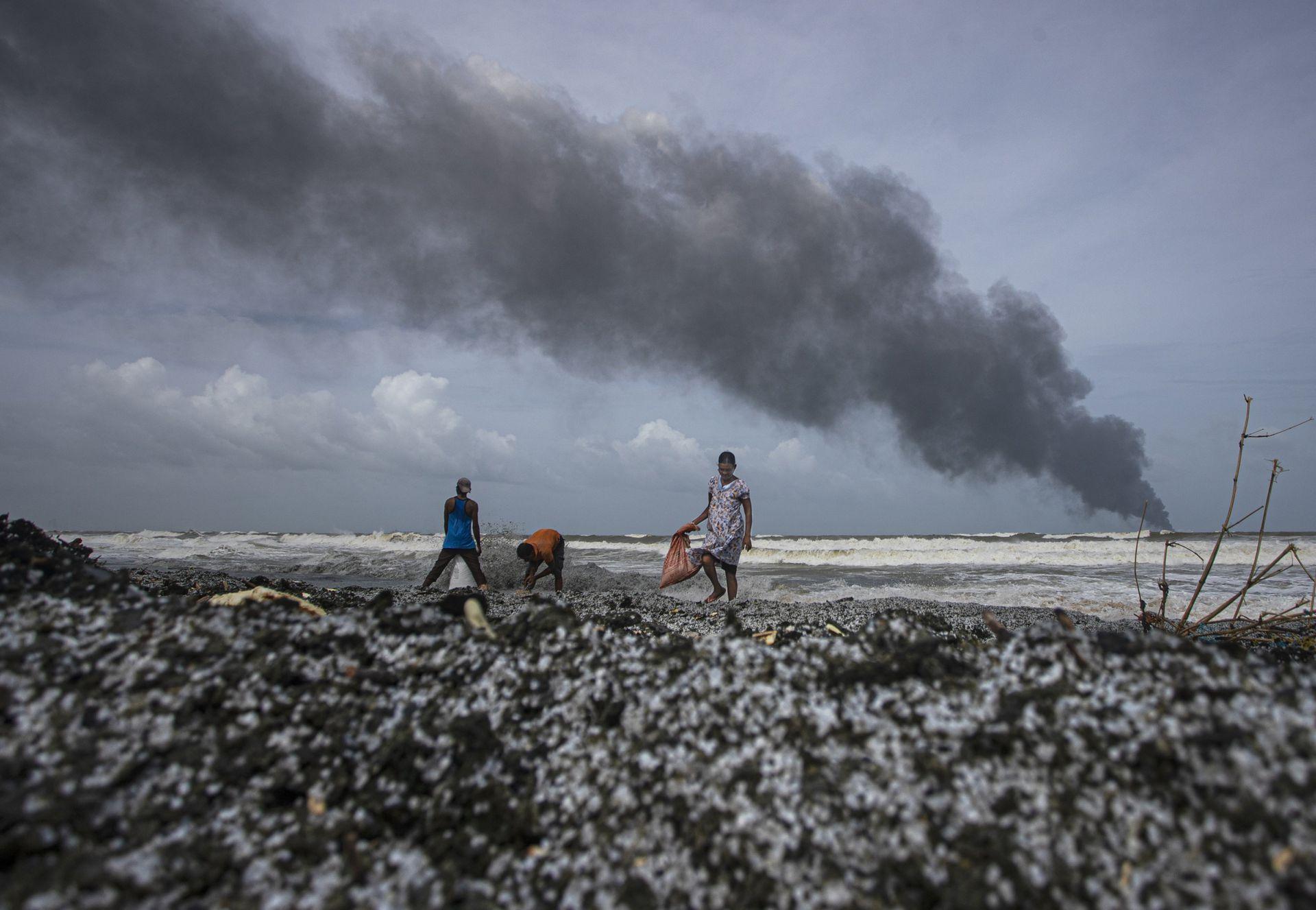 Algunas personas tratan de rescatar objetos entre los restos quemados que llegan a la costa de Sri Lanka