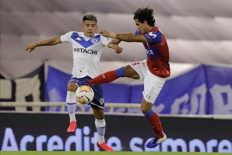Thiago Almada, quien debió retirarse del campo por un problema muscular, pelea por la pelota con Ignacio Saavedra, de Universidad Católica.