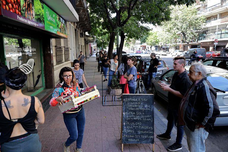 Espera para ingresar a una verdulería sobre la Av. Díaz Vélez; muchos negocios permiten hacer pedidos por Whatsapp para ir sólo a retirarlos