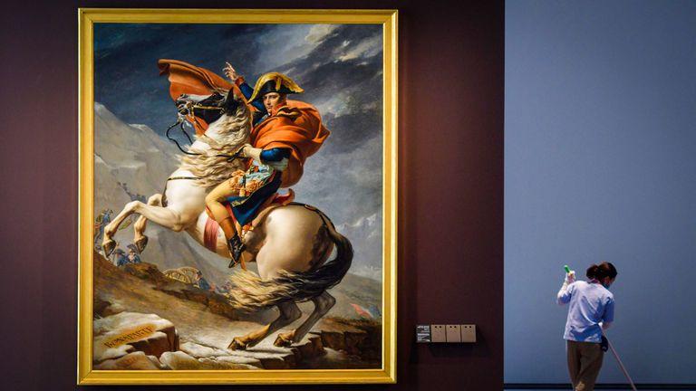 """Una empleada de limpieza junto a la pintura titulada """"Napoleón Bonaparte, primer cónsul, cruzando los Alpes"""" del artista francés Jacques-Louis David"""