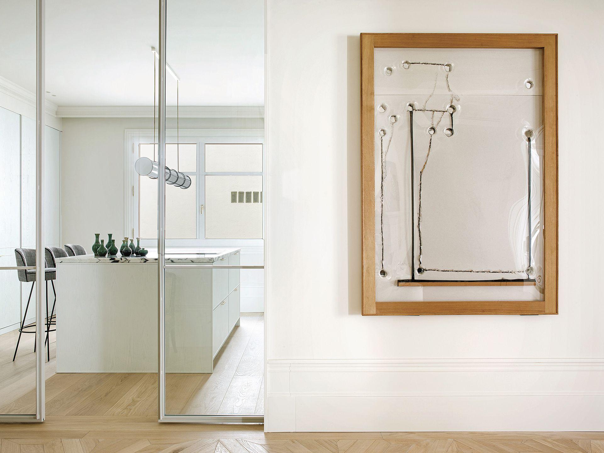 La entrada de la cocina tiene puertas de vidrio corredizas, que establecen un límite entre el parquet y el entablonado.
