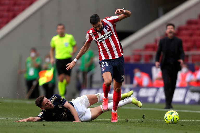 Yannick Carrasco lucha por la pelota con Enrique Barja durante un partido entre el Atlético Madrid y el Osasuna.