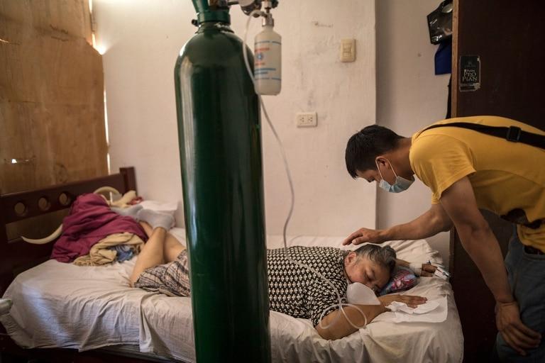 Elena Ruiz, de 53 años, respira oxígeno como parte de su tratamiento de recuperación del COVID-19, mientras su hijo Antony la cuida, en Lima, Perú