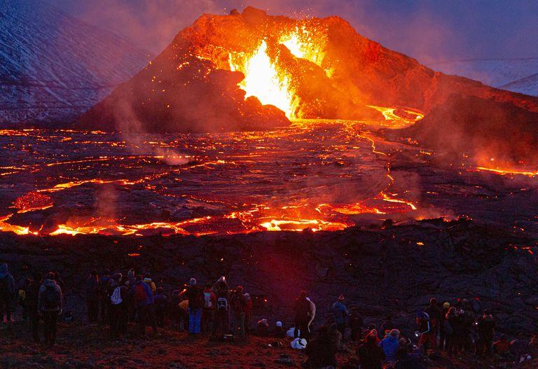 Las figuras de las personas están iluminadas por el resplandor de la lava