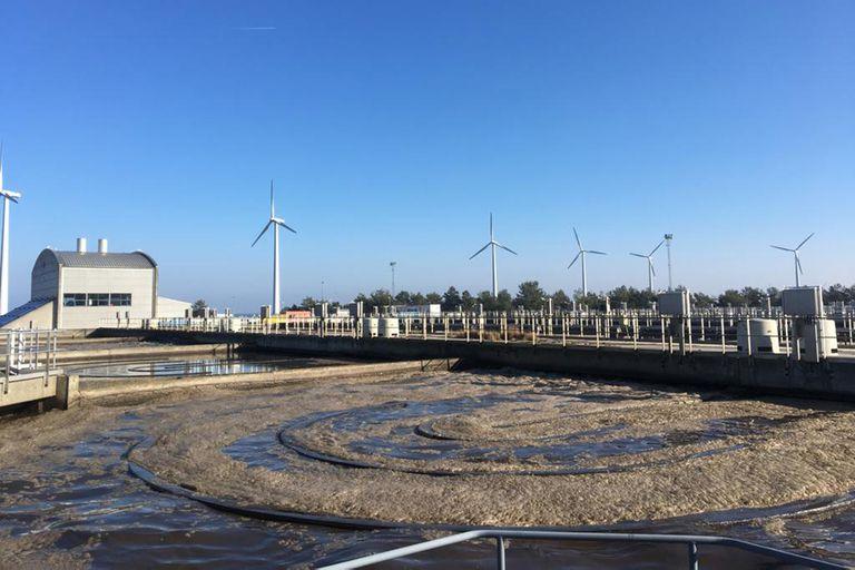 La mayor planta de tratamiento del agua en Copenhague y, detrás, molinos eólicos