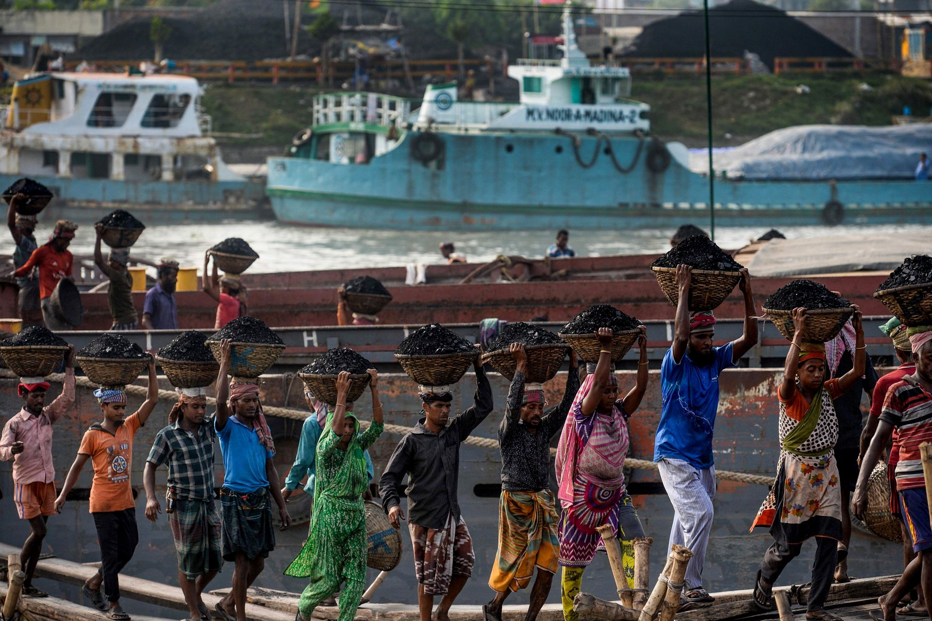 Trabajadores descargan carbón de un buque en Gabtoli, en las afueras de Dhaka, la capital de Bangladesh