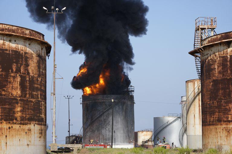 Bomberos trabajando para extinguir un incendio en una instalación petrolera en la localidad sureña de Zahrani, al sur dl puerto de Sidon, Líbano, el lunes 11 de octubre de 2021. (AP Foto/Hassan Ammar)