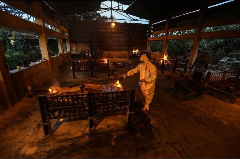 Familiares y empleados municipales practican los ritos fúnebres a las víctimas de covid-19 en un centro de cremación en Bombay