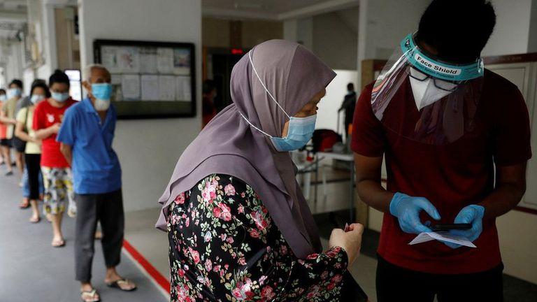 Los residentes de una urbanización pública hacen cola para las pruebas obligatorias de coronavirus en Singapur el 21 de mayo de 2021