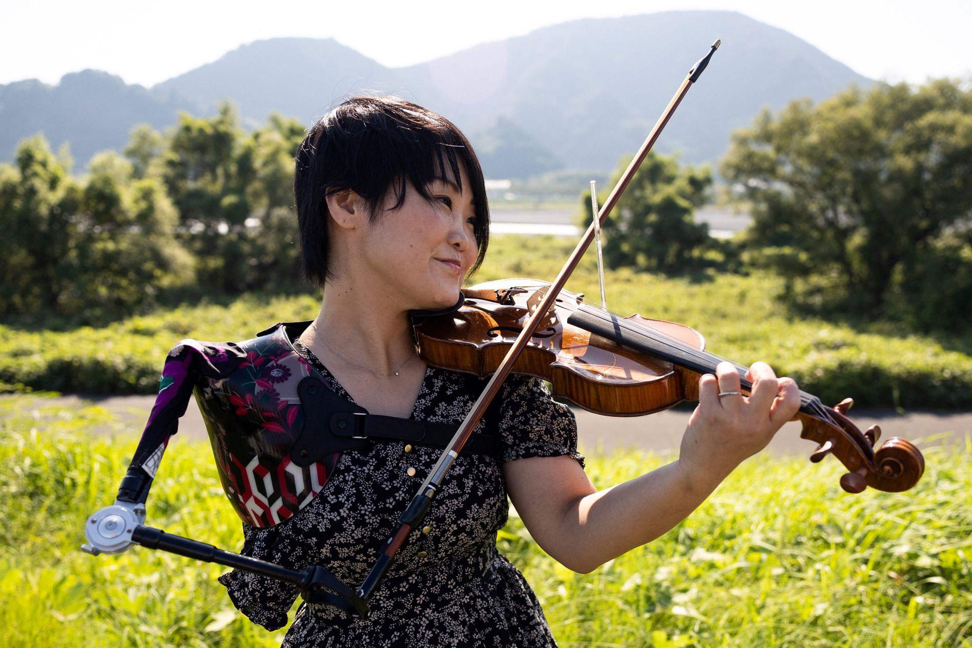 La música japonesa Manami Ito, que también es enfermera titulada y ex nadadora paralímpica, toca el violín con su brazo protésico durante una sesión de fotografía en Shizuoka.