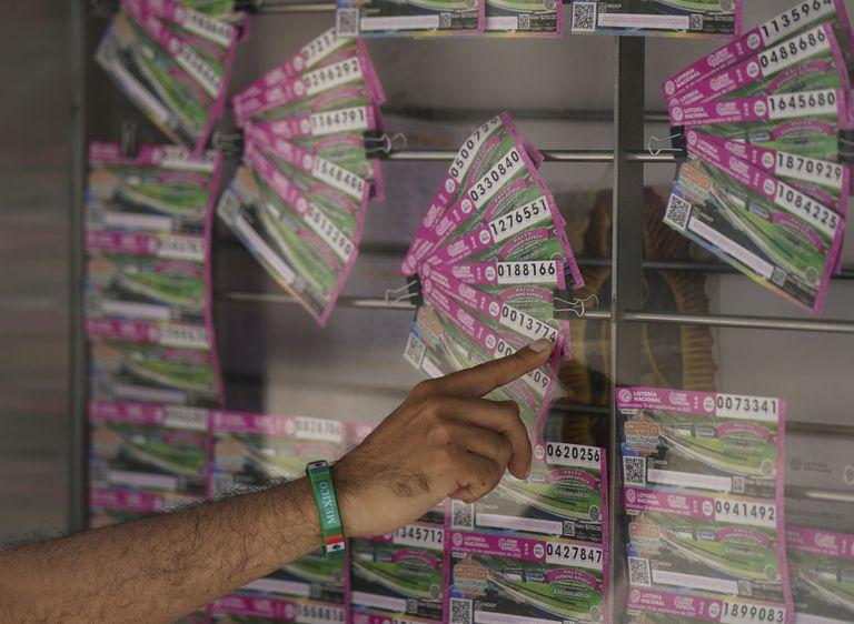 """Un cliente señala un boleto de lotería que quiere comprar en la Ciudad de México, el lunes 13 de septiembre de 2021. La lotería de México está regalando como premios propiedades incautadas a los narcotraficantes, entre ellas una casa que perteneció a Joaquín """"El Chapo"""" Guzmán. (AP Foto/Fernando Llano)"""