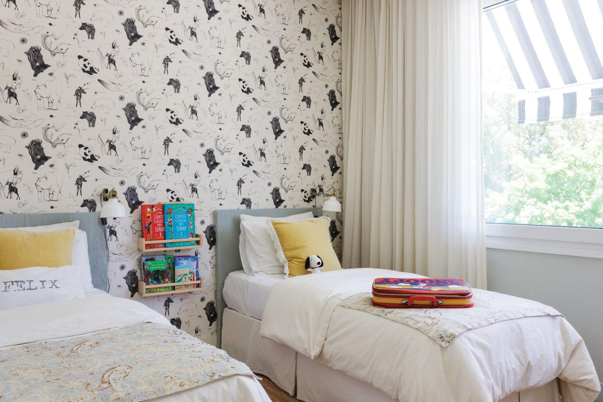 Wallpaper con motivos de animales (Picnic). Respaldos de madera con funda de lino belga color celadón. Funda de lienzo de algodón crudo (Zara Home). Mantas de lino estampado (ABC Home). Estantes para apoyar libros (Ikea).