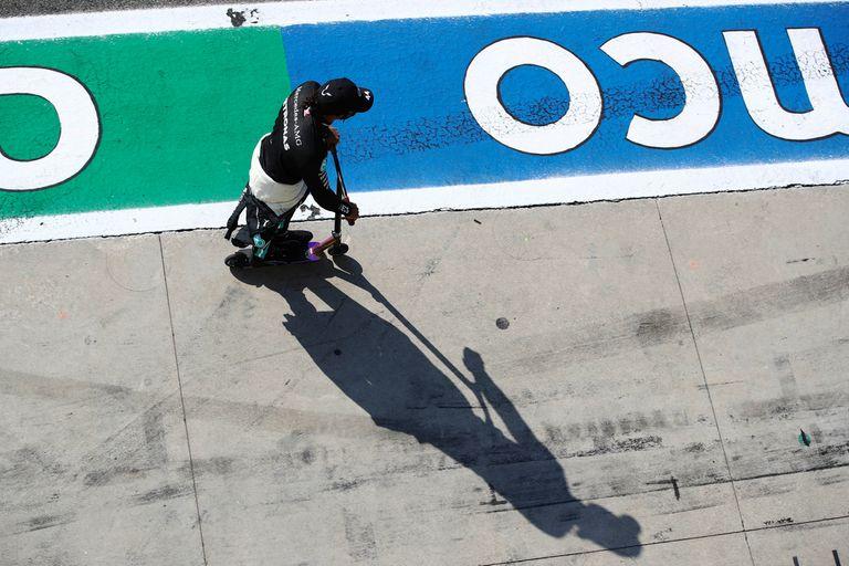El piloto de Mercedes Lewis Hamilton se dirige en monopatín a revisar el fallo que lo obligó a retrasarse diez segundos