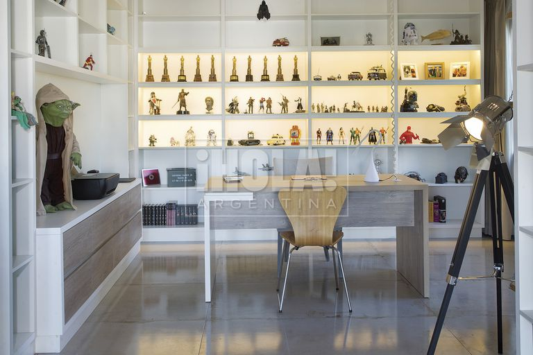 La oficina cuenta con un segundo escritorio en la que una gran estantería expone y atesora sus muñecos de la infancia, figuras de colección, recuerdos, fotos familiares y sus Martín Fierro.