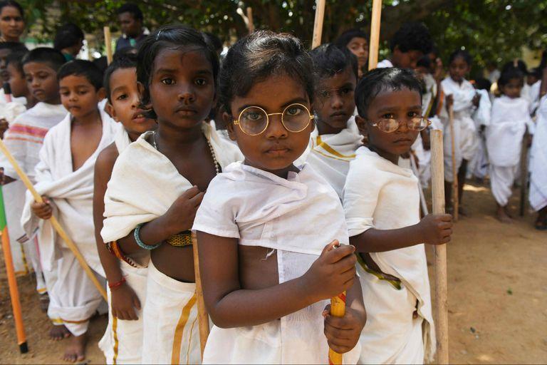 Estudiantes vestidos como Mahatma Gandhi hicieron una muestra en su escuela por el aniversario del nacimiento del activista