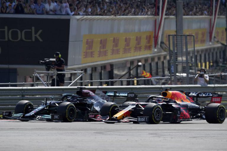 Lewis Hamilton (izq) y Max Verstappen pelean por la punta en el arranque del GP Británico el 18 de julio del 2021 en Silverstone. Poco después se tocarían las ruedas y Verstappen se saldría de la pista y se estrellaría contra una barrera de neumáticos, quedando afuera de la carrera. Hamilton fue castigado con diez segundos, pero de todos modos ganó la carrera. Verstappen se siente confiado en que su vapuleado cuerpo está listo para reanudar una intensa batalla en Fórmula Uno con Hamilton en el Gran Premio de Hungría el domingo. (AP Foto/Jon Super)