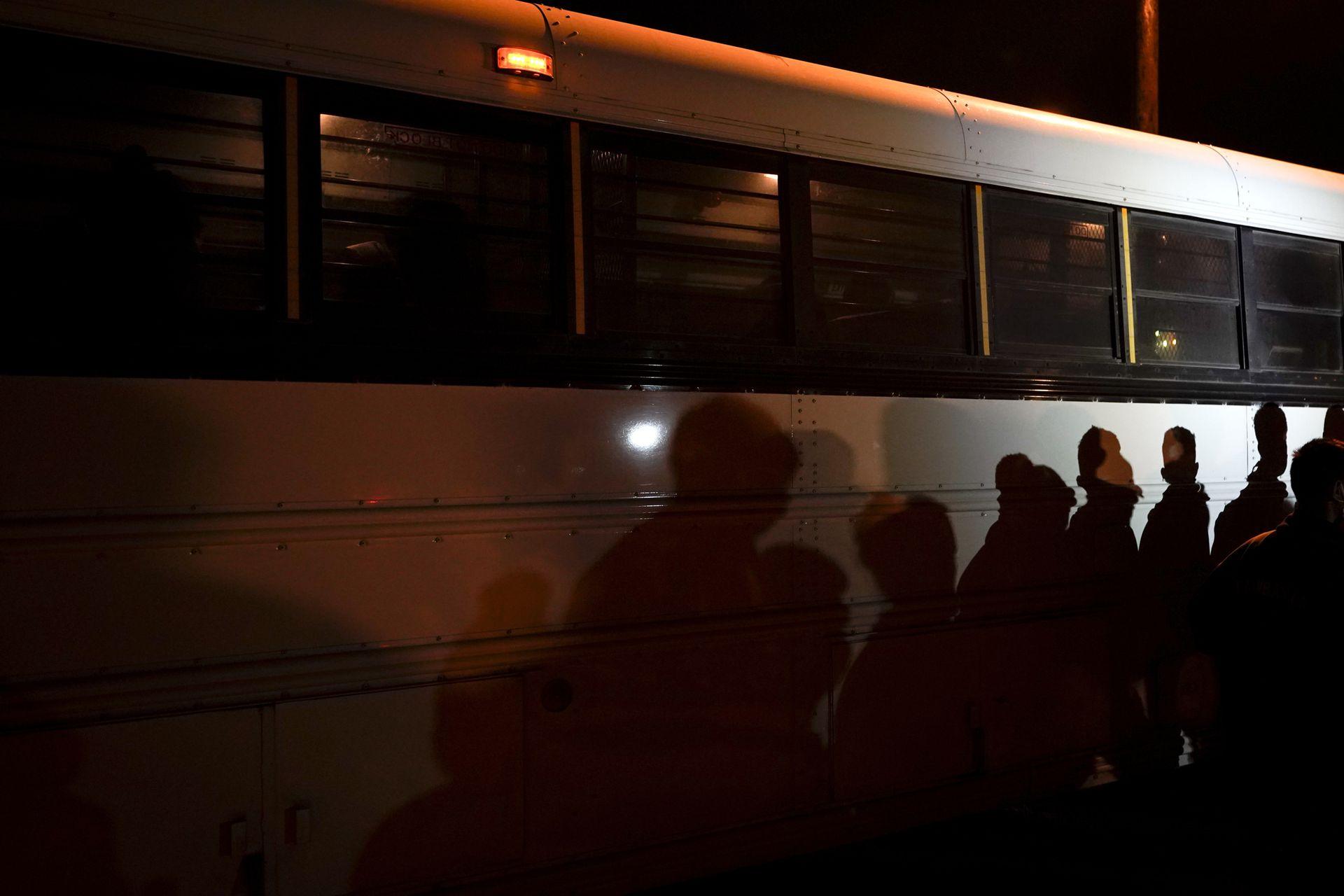 Las sombras de los migrantes alineados se proyectan a lo largo de un autobús, después de entregarse al cruzar la frontera entre Estados Unidos y México en Roma, Texas