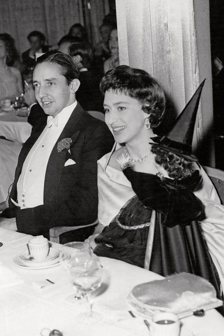 Con un vestido strapless y gargantilla de diamantes, Margarita sostiene en brazos una bruja, acompañada por Billy Wallace (fue su prometido hasta que ella rompió el compromiso cuando él le confesó una infidelidad) durante la fiesta de Halloween celebrada en el hotel Dorchester, en 1957.